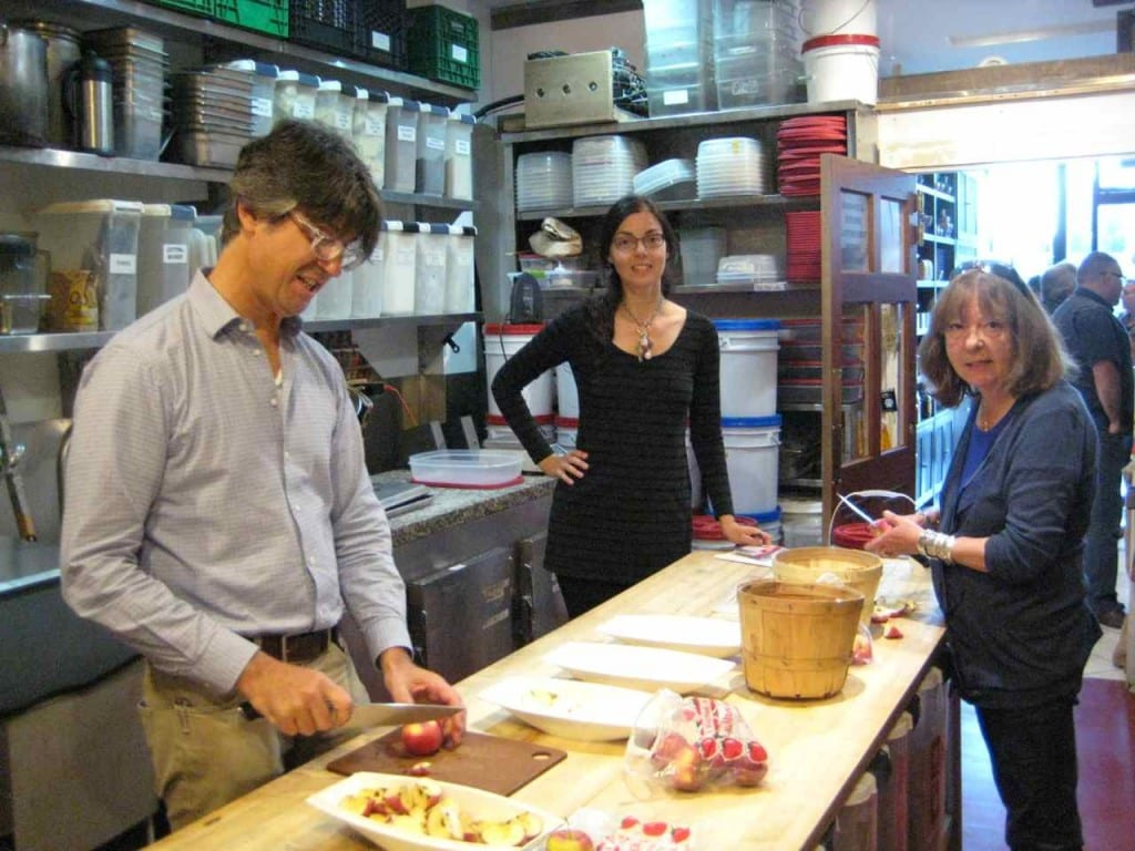 Paul DeCampo, Susan Poizner, and Gaye Trombley in the kitchen of Chocosol Traders preparing the tasting apples.