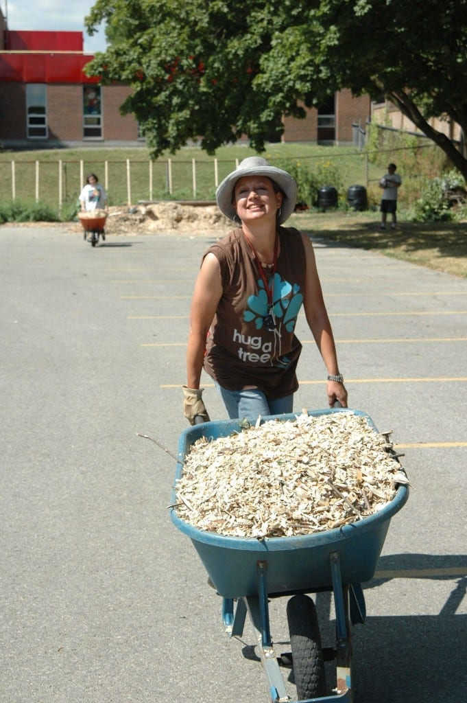 Virginie Gysel helps mulch the new trees at the Harcourt Community Orchard.