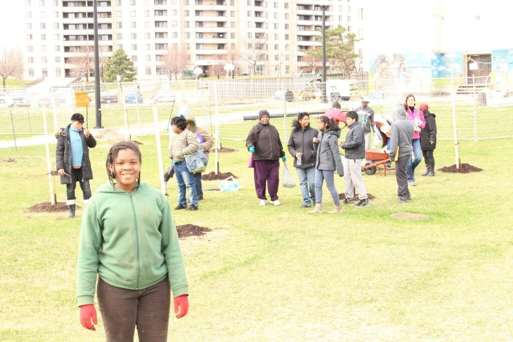 """Isioma (front) and the other students planting 18 fruit tree """"whips"""" on the San Romanoway property in Toronto. All of the students have signed on to an Adopt-a-Tree program."""